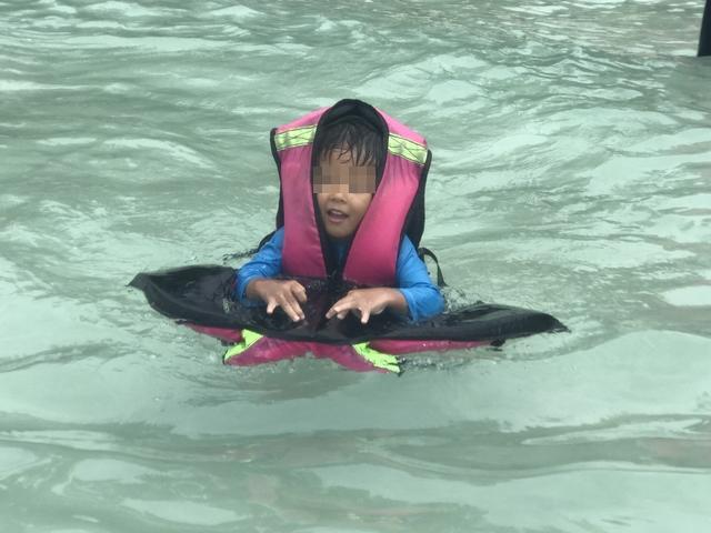 子供ライフジャケットに乗って泳ぐ.jpg
