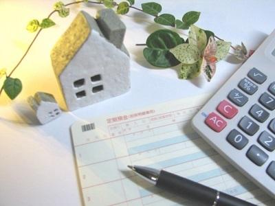 電卓と通帳と家の模型