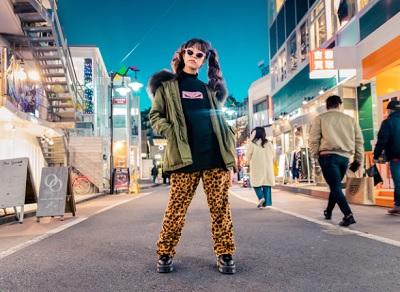 派手なファッションで道に立つ女性