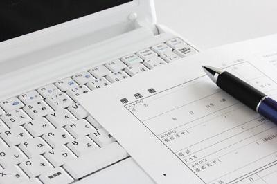 履歴書とパソコンとペン